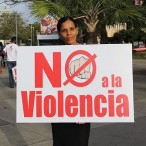 "Woman with a sign that says, ""No to violence"""
