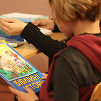 Child reading an illustrated Bible